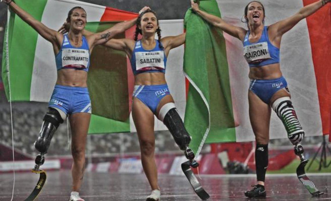 Fotografía de las tres atletas italianas que hicieron el 1, 2, 3 en la carrera de 100 metros. Las tres son mujeres jóvenes, que tienen la amputación de una pierna -dos de ellas la izquierda y la otra la derecha- y llevan prótesis hasta el muslo. Las tres visten uniforme de competencia, color azul claro, el top es muy corto y el short es corto. Cada una de las jóvenes tiene una bandera de Italia, verde, blanca y roja, y la pasan por atrás de su cabeza mientras alzan los dos brazos.