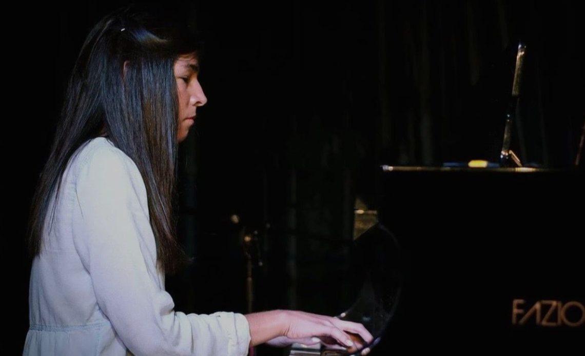 Fotografía de perfil de Marcela Bastida, una joven pianista de cabello largo semi recogido de la frente y le cae sobre la espalda y el hombro hacia el frente. Viste ropa color claro que resalta en la imagen oscura donde se aprecian sus manos sobre el teclado de un piano negro.