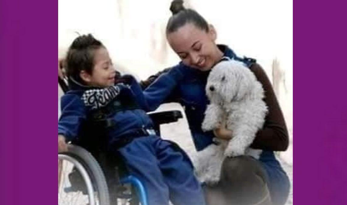 Fotografía de una mujer joven, de cabello oscuro, recogido atrás de la cabeza, que ladea el rostro hacia el lado derecho donde se encuentra un niño, de unos cuatro o cinco años, sentado en una silla de ruedas. La mujer sostiene a un perro blanco, peludito, que mira fijamente al niño, quien al igual que la mujer esboza una gran sonrisa.