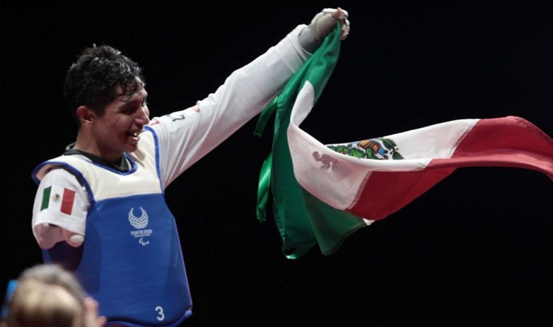 Fotografía de un hombre joven, con traje blanco de combate de TaeKwonDo y peto azul, tiene el cabello oscuro y está casi de perfil. Con el brazo izquierdo, el único que tiene, ondea una bandera mexicana, cuyos colores destacan más en el fondo negro en que fue captada la imagen.
