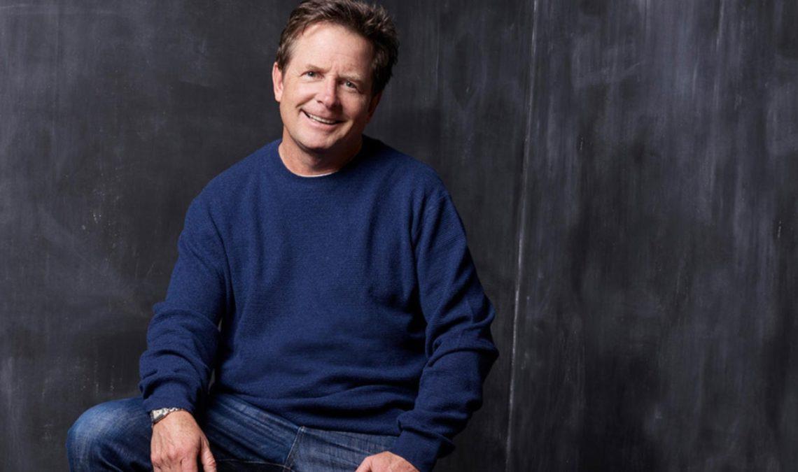 Fotografía del actor Michael J. Fox, un hombre maduro, de tez muy clara, cabello rubio oscuro, sentado frente a una pared oscura con textura que crea betas más claras; él ladea un poco la cara hacia la izquierda y sonríe. Viste un suéter azul holgado, y pantalones de mezclilla. Sus manos descansan sobre cada una de sus piernas.