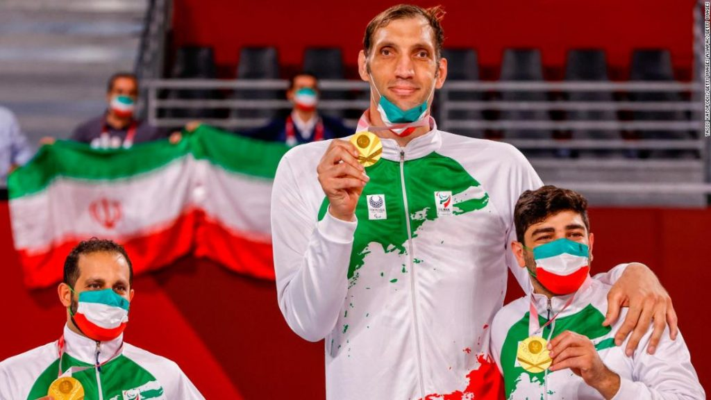 Fotografía de tres de los integrantes del equipo de voleibol varonil de Irán. Los hombres de las orillas llegan apenas arriba del codo al jugador que está en medio y mide 2.46 metros. Todos muestran sus medallas, y visten uniformes con la bandera de su país: blanco con estampado verde y rojo.