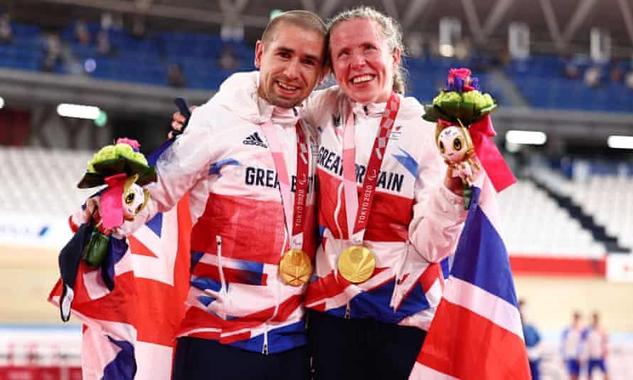 Fotografía de un hombre y una mujer, que son esposos y campeones paralímpicos en ciclismo. Los dos visten uniforme de Gran Bretaña, en los colores de su bandera: blanco, rojo y azul. Ambos se abrazan mientras lucen sus medallas de oro, y sonríen.