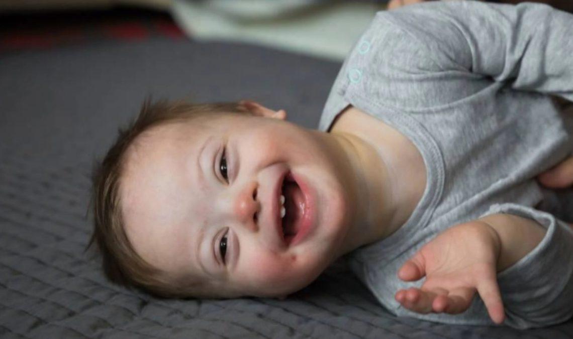 Fotografía de un bebé de menos de un año que tiene síndrome de Down, está recostado sobre su lado izquierdo sobre una superficie acolchada color gris de tal manera que la fotografía se ve de lado. El bebé tiene tez blanca, cabello rubio y una enorme sonrisa. Estira su brazo izquierdo y usa una especie de camiseta gris de manga larga.