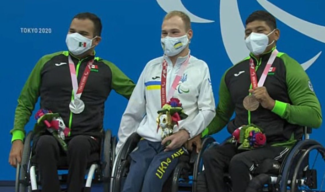 Podio de triunfadores. Tres nadadores paralímpicos. Al centro, el ucraniano, con la medalla de oro y su uniforme deportivo de pants y chamarra blanca; a sus lados, dos nadadores mexicanos, con sus pants negros y chamarra negra con mangas verdes. Los tres usan cubrebocas y, también, los tres son usuarios de sillas de ruedas.