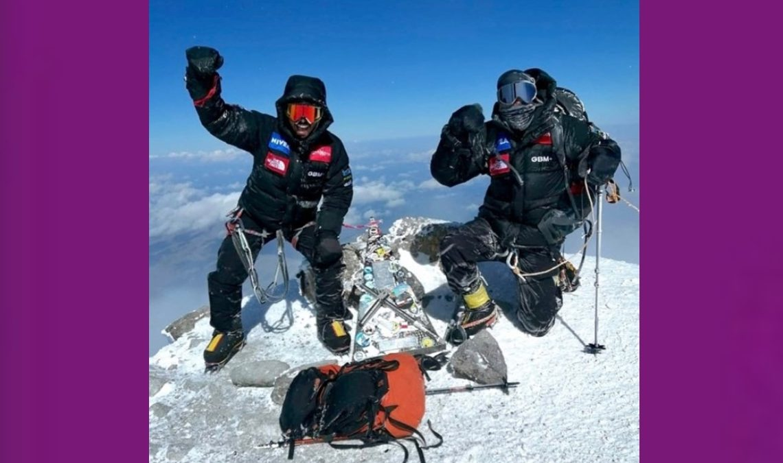 Fotografía de dos hombres alpinistas en la cima del monte Elbruz, que está cubierta de nieve. Los dos tienen trajes de protección color negro de la cabeza a los pies, pero alzan sus brazos en señal de triunfo. Adelante está una de sus mochilas, color anaranjado con negro, y sus bastones y piolets de metal. Detrás luce el cielo azul y algunas nubes.