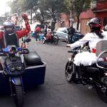 Fotografía de dos personas que conducen motocicletas adaptadas para personas con discapacidad motriz. De espalda se ve una mujer vestida de blanco con un casco de protección, de frente está un hombre, con una sudadera roja, casco de protección, y levanta los brazos donde sostiene unas cadenas tricolor, de las que se usan para adornar durante las fiestas patrias en México. Las dos motocicletas también llevan algunos adornos y se ubican en una calle.
