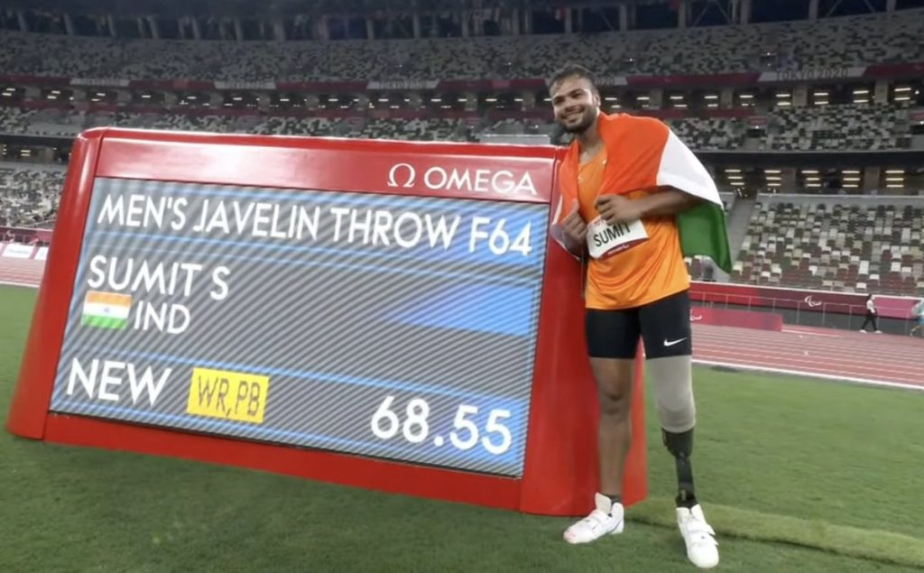 El medallista de India Sumit Antil al lado de la parrilla que muestra el tiro que logró en jabalina, de 68.55 metros y que le valió, además del oro, los récords olímpico y mundial. El atleta es alto, tiene amputada la pierna derecha y lleva una prótesis. Viste shorts pegados color negro y playera anaranjada. Cubre su espalda con la bandera de su país: anaranjada blanco y verde. Es un hombre joven, de cabello barba y bigote oscuro, y sonríe.