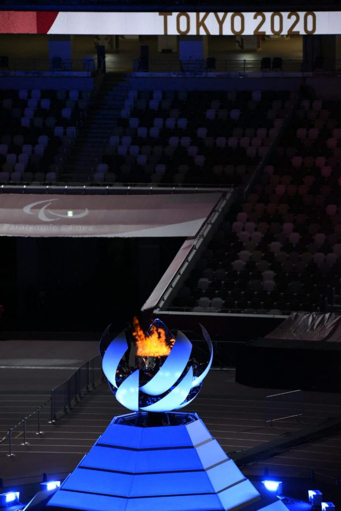 Fotografía del fuego paralímpico que representaba al Monte Fuji sobre una estructura piramidal que es iluminada por luces azules, que contrastan con la oscuridad del estadio. La imagen se muestra en la parte inferior de la fotografía, hacia arriba, en un plano medio, se ve el logotipo de los Juegos Olímpicos y aún más arriba, en lo más alto del estadio, las palabras Tokyo 2020.