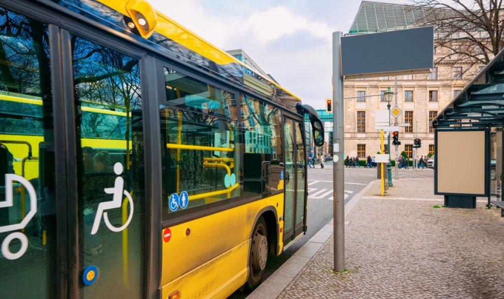 Fotografía de un paradero de autobús en Berlín, Alemania, que muestra a uno de los famosos autobuses que en sus puertas tiene los iconos de accesibilidad: una silla de ruedas con una persona, que indica que ese transporte es incluyente y que las personas con discapacidad motriz pueden abordarlos con facilidad. En la fotografía, además del paradero, a lo lejos se alcanza a ver uno de los edificios de esa ciudad.